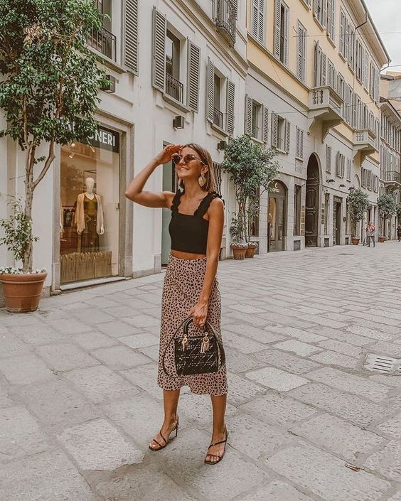 a black ruffle strap crop top, a pink polka dot midi skirt, strappy heels and a black bag for summer
