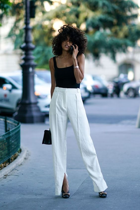 a black strap top, white linen trousers with slits, chic black shoes and a black bag
