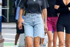 a black t-shirt, blue denim bermuda shorts, black trainers, a mini baguette bag