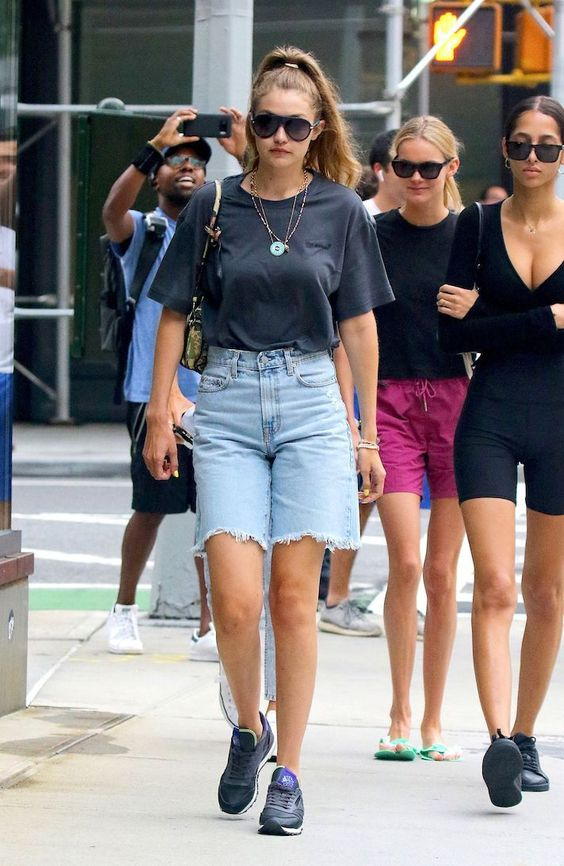 a black t shirt, blue denim bermuda shorts, black trainers, a mini baguette bag