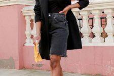a black top, a blazer oversized blazer, black denim Bermuda shorts, black strappy heels and statement earrings