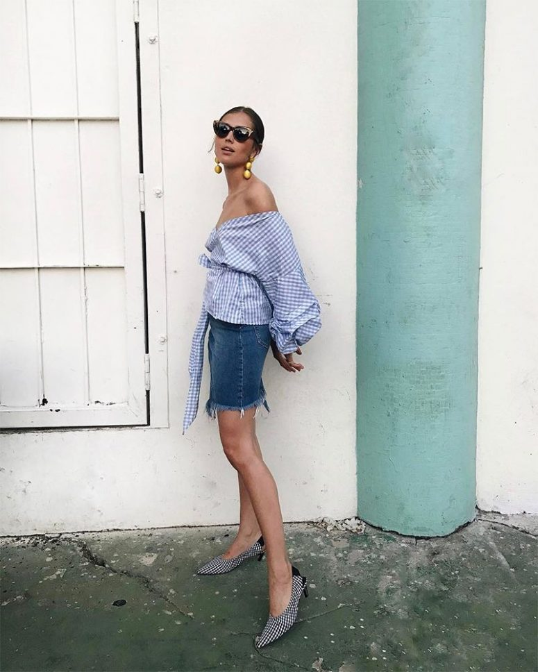 a blue denim skirt, a blue off the shoulder gingham blouse with puff sleeves, gingham shoes and statement earrings