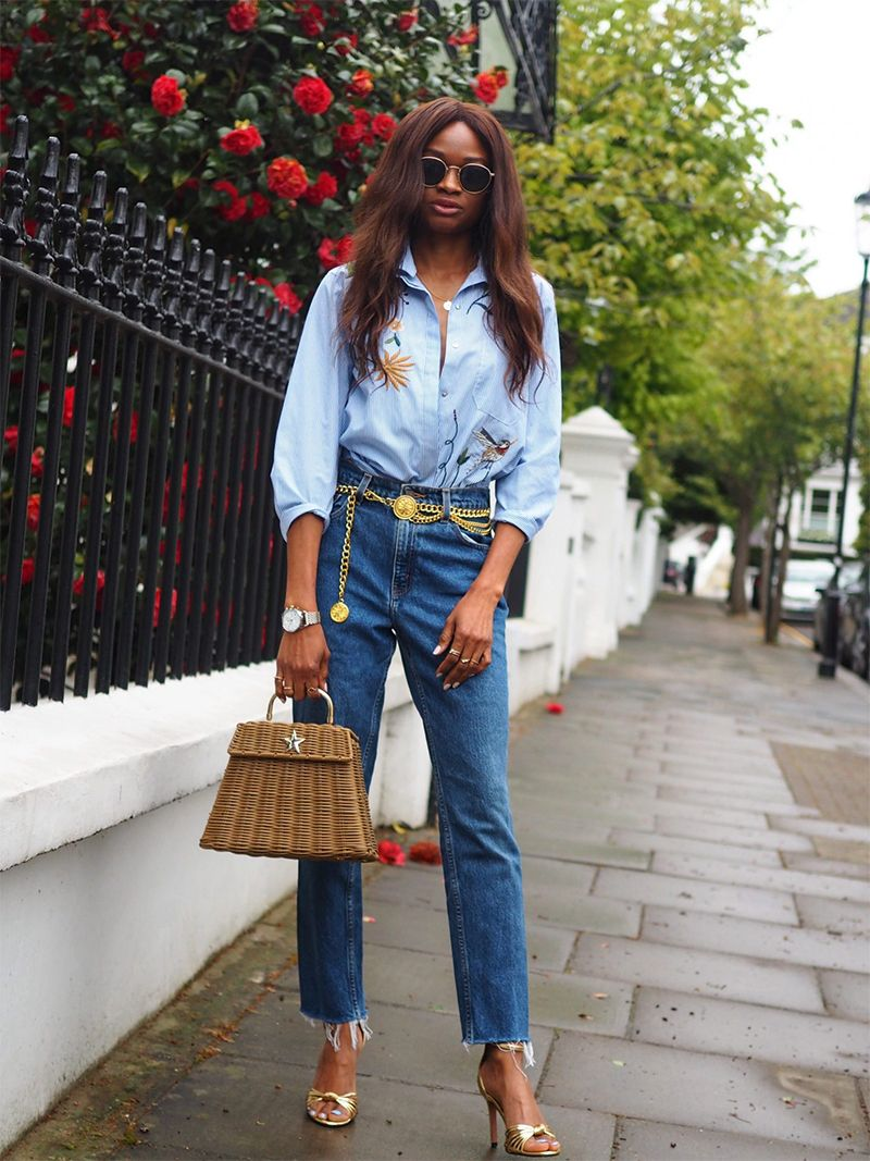 a blue floral embroidered shirt, blue jeans, a gold chain belt, gold heels and a straw bag