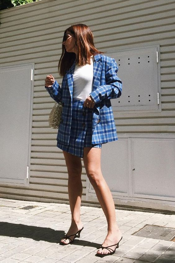 a blue plaid suit with an oversized blazer and a wrap mini skirt, a white top, black strappy kitten heels and a white woven bag