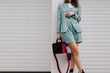 a blue printed shorts suit with a printed tee, white ankle strap shoes with buckles and a burgundy bag