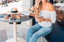 a blue striped off the shoulder top, blue cropped jeans, grey slipper mules and a hat for a summer coffee date