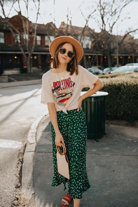a blush printed t-shirt, a green floral slip skirt, red slippers, a hat and a catchy bag