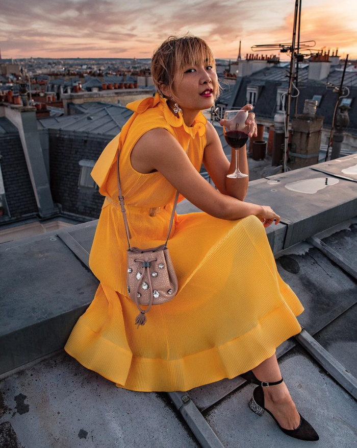 a bold yellow midi dress with no sleeves and ruffles, black heels and a nude embellished bag