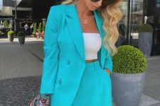 a bright suit with an oversized blazer and shorts, a white bandeau top, a white mini bag and statement earrings