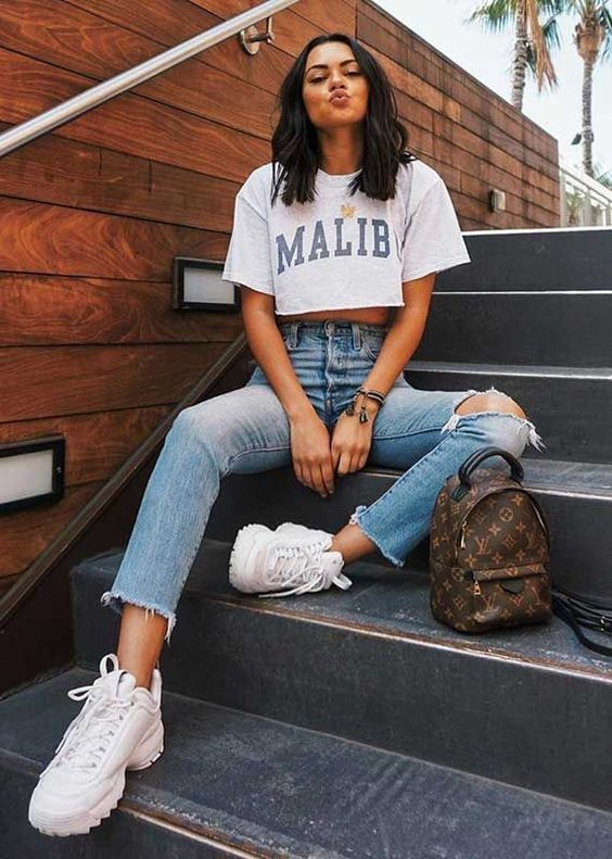 a casual look with a cropped tee, blue ripped jeans, white trainers and a brown printed backpack