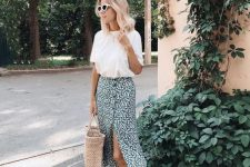 a casual outfit with a white t-shirt, a green printed midi skirt, a straw bag and birkenstocks