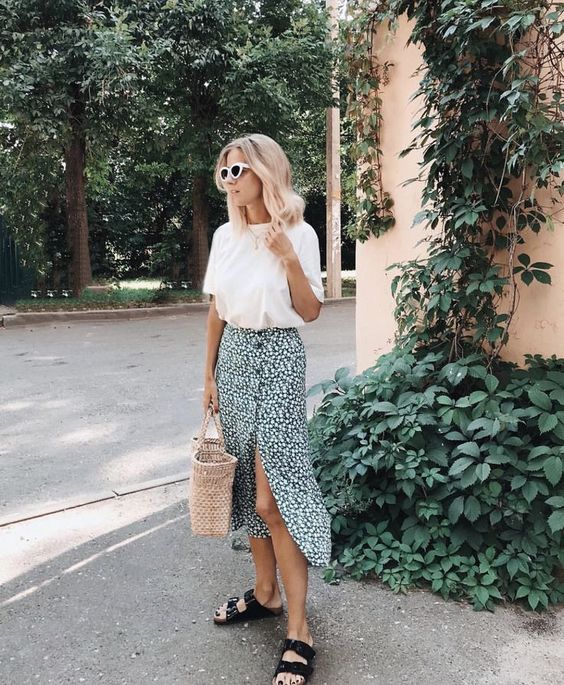 a casual outfit with a white t shirt, a green printed midi skirt, a straw bag and birkenstocks