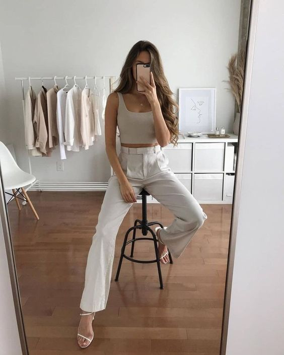 a chic and minimal summer look with a grey crop top, white high waisted trousers and white strappy shoes