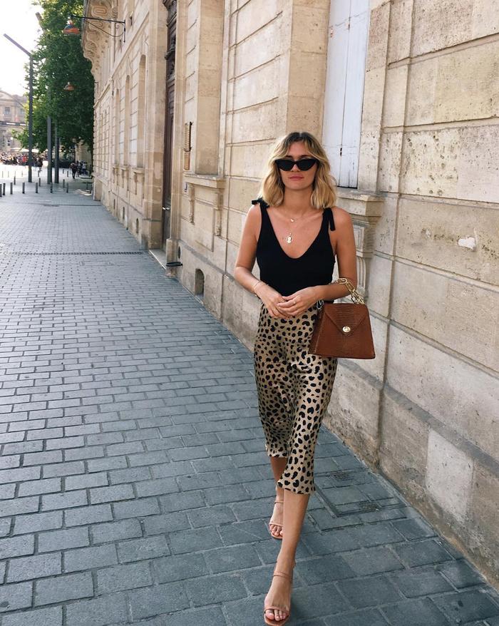 a chic summer date look with a black deep cut top, a leopard print slip skirt, nude heels and a cognac bag