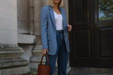 a chic summer look with a white top, blue high waisted jeans, a coastal blue blazer, white strappy kitten heels and a bucket bag