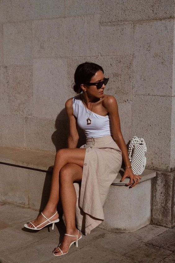 a chic summer outfit with a white one shoulder top, a linen button up skirt, white strappy heels and a bead bag