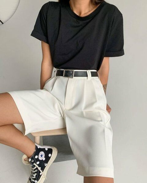 a classic casual look with a black t-shirt, white bermuda shorts, a black belt and black and white sneakers