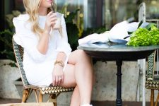 a cool white mini dress with a high neckline, ruffles, long sleeves, platform sneakers and a neutral bag
