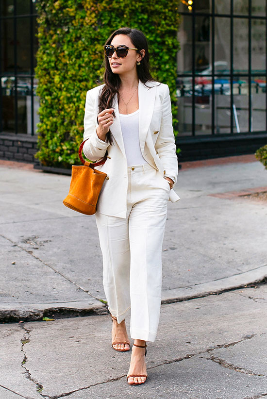 a creamy linen suit, a white top, an amber bucket bag and brown strap heels