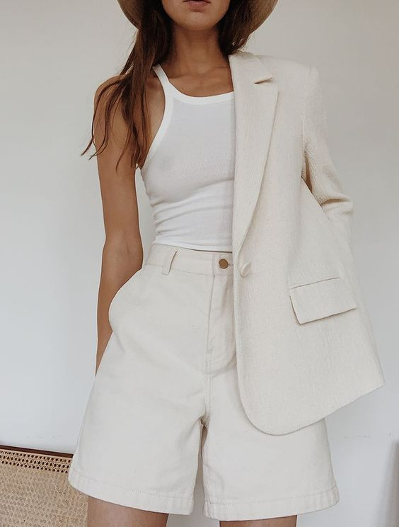 a creamy short suit with high waisted shorts and an oversized blazer and a white halter neckline top
