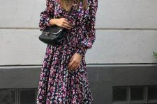 a dark floral maxi dress with long sleeves and a high neckline, a black bag and black strappy kitten heels
