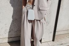 a dove grey oversized pantsuit, a white bra top, a white bag and heels for spring or summer
