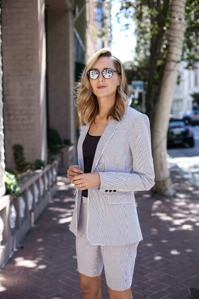 a fitting striped Bermuda short suit with a black top and mirror glasses is a chic idea