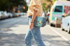 a floral printed blouse with puff sleeves, blue jeans, blue heeled mules and a blue and green bag