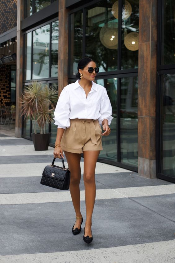 a glam look with an oversized white shirt, tan high waisted mini shorts, black flats and a black bag