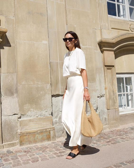 a gorgeous look with a white oversized t-shirt, a slip maxi skirt, black slippers and a leather bag