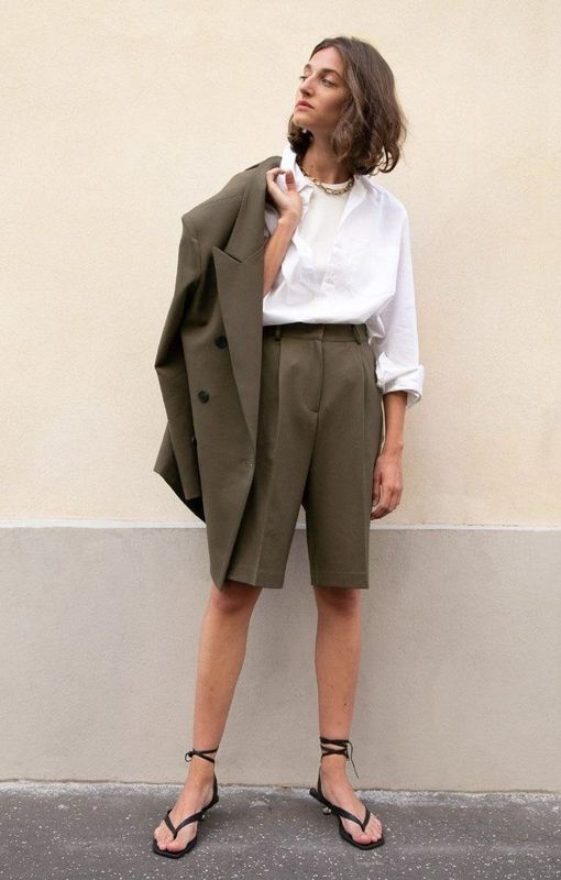 a graphite grey short suit with an oversized blazer, Bermuda shorts, a white shirt and black sandals