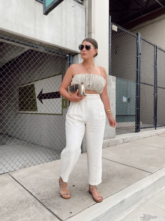 a grey crop top, white linen trousers, embellished sandals, a metallic bag and oversized sunglasses
