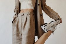 a grey linen short suit with Bermuda shorts, an oversized blazer, white trainers and a white crop top for work