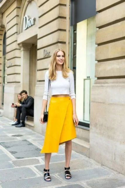 a grey long sleeve crop top, a yellow wrap asymmetrical skirt, black lacquer strap sandals and a black bag