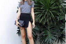a grey t-shirt, a black mini skirt with a slit, black strappy kitten heel sandals, a black bag