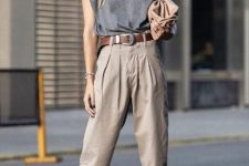 a grey t-shirt with accented shoulders, taupe pants, strappy sandals and a tan clutch plus a brown belt