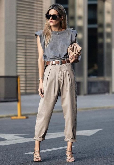 a grey t shirt with accented shoulders, taupe pants, strappy sandals and a tan clutch plus a brown belt