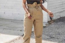a grey thick strap top, tan paperbag waist pants, ankle bow heels and a wooden bag