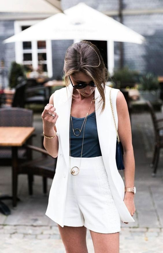 a grey top, white shorts and a white sleeveless blazer plus layered necklaces and a navy bag