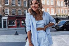 a lovely pastel blue suit with a blazer, mini shorts, a crop top and a pink and black bag