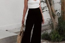 a minimalist look with a white top, black culottes, black ankle strap shoes and a straw bag