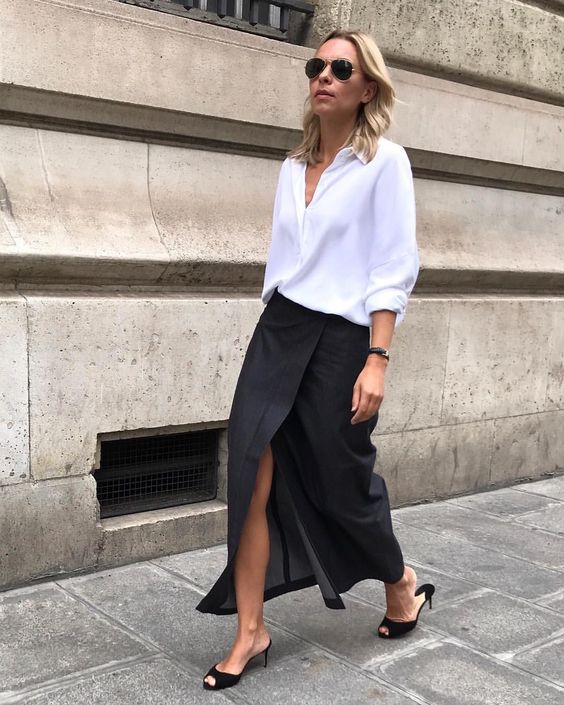 a minimalist outfit with an oversized white shirt, a black wrap maxi, black kitten heels and sunglasses