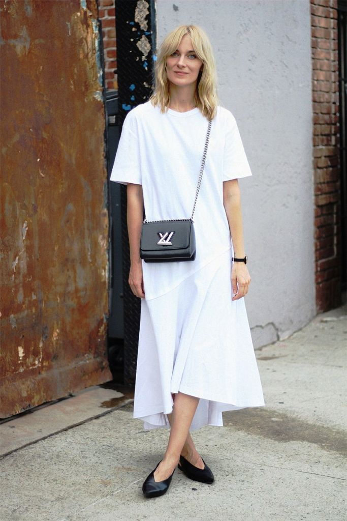 a minimalist summer outfit with a white midi t-shirt dress with a high neckline, short sleeves and an asymmetrical skirt, black slingbacks and a black bag