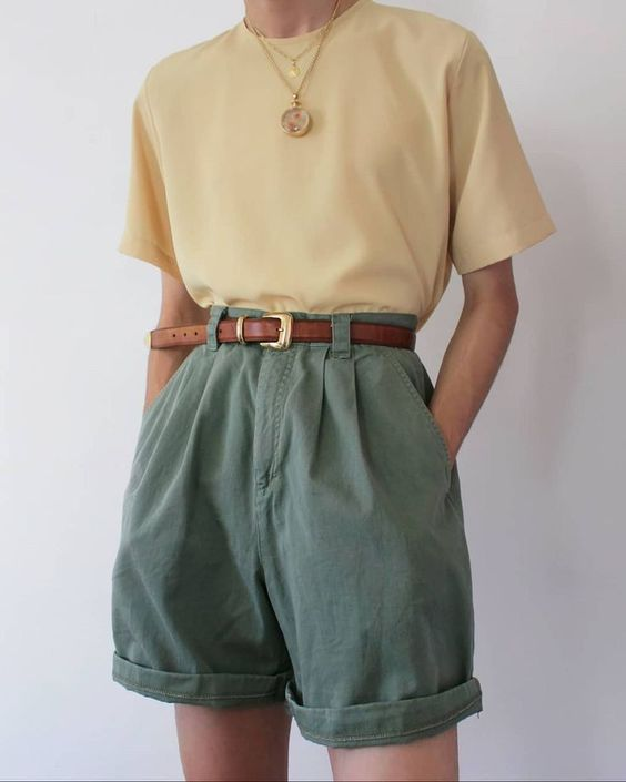 a minimalist summer outfit with a yellow t shirt, green pleated shorts, a brown belt and necklaces is easy to realize