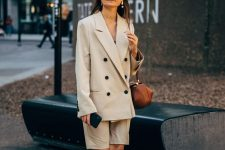 a neutral short suit with a double-breast blazer and Bermuda shorts, a black top, orange heels and a brown bag