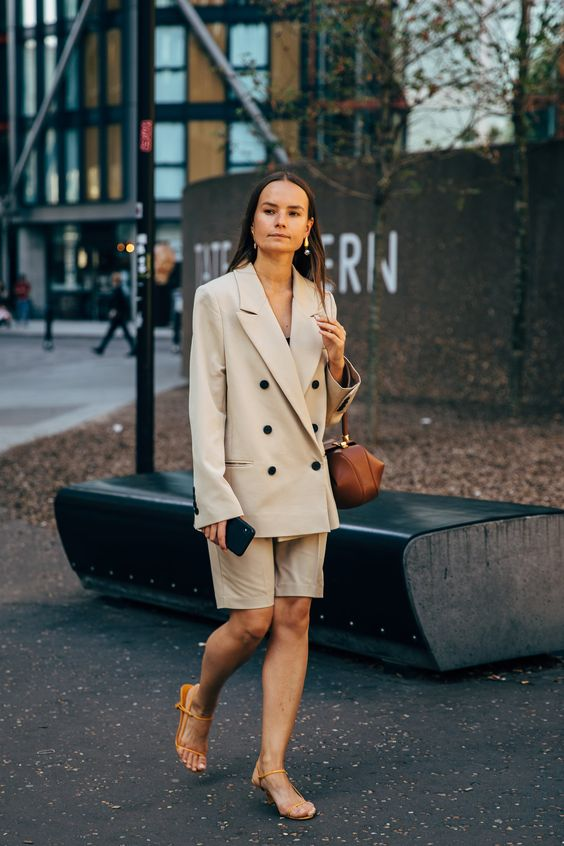 a neutral short suit with a double breast blazer and Bermuda shorts, a black top, orange heels and a brown bag