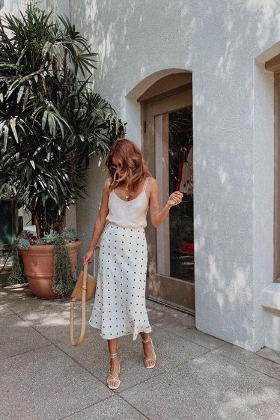 a neutral spaghetti strap top, a polka dot midi skirt, white strappy heels and a tan bag