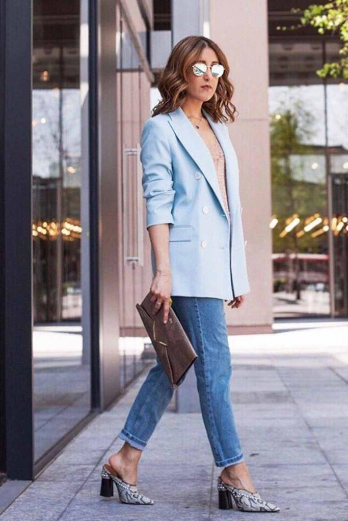 a nude top, blue jeans, an oversized blue blazer, snakeskin print mules and a brown clutch