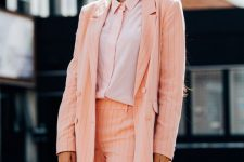 a peachy pink striped short suit, a pink shirt, a baguette bag and trendy retro sunglasses