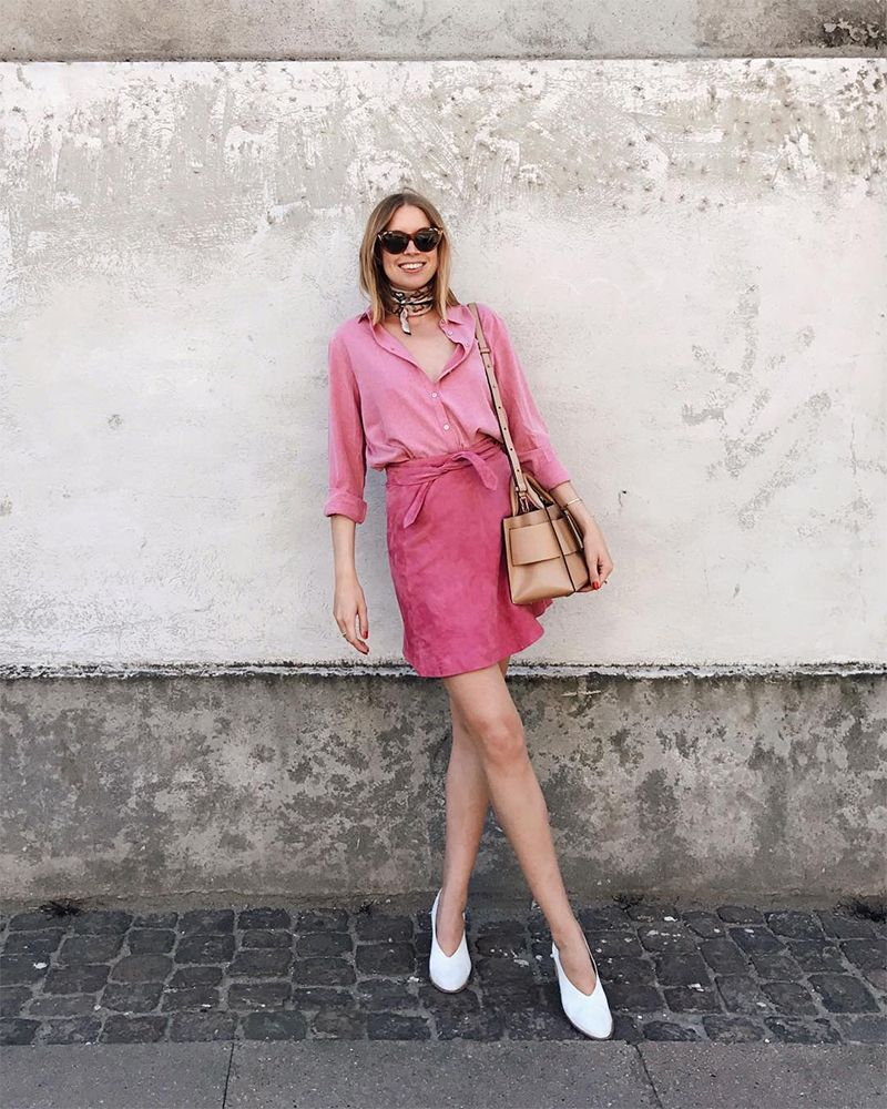 a pink shirt, a pink suede looking skirt, a tan bag and white shoes plus a handkerchief for summer